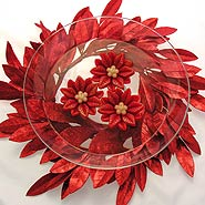 Red holiday bay leaf candle centerpiece with poisettia candles
